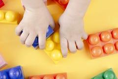 玩具砖 儿童手采取玩具大厦bloks 在黄色背景的玩具砖 免版税库存照片