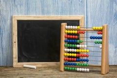 玩具算盘和空白的黑板 免版税库存图片