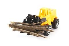 玩具铲车运载的木头 免版税库存图片