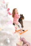 玩具马的小女孩在白色圣诞节树 免版税图库摄影