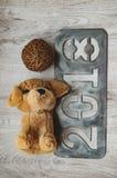 玩具` s狗作为2018个新年的标志与圣诞节的在金属和得体归因于新年` s题字2018年被雕刻 库存照片