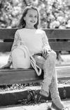 玩得高兴 放松在步行期间的女孩在公园在樱花附近 概念放松 有袋子或背包的逗人喜爱的孩子 免版税库存图片