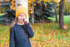 玩捉迷藏的小女孩在树附近  免版税库存图片