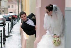 玩捉迷藏的新娘和新郎 免版税库存照片
