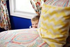 玩捉迷藏的镶边套头衫的可爱的小男孩在房子里 免版税图库摄影