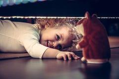 玩捉迷藏的滑稽的逗人喜爱的微笑的婴孩在与玩具仓鼠的床下在葡萄酒样式 免版税库存照片