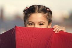 玩捉迷藏 掩藏从某人的滑稽的少女 美丽的明亮的眼睛 有打比赛的伞的女孩 库存照片