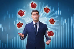 玩杂耍与在企业概念的piggybanks的商人 免版税库存照片