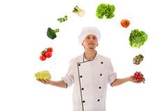 玩杂耍与新鲜蔬菜的厨师 免版税图库摄影