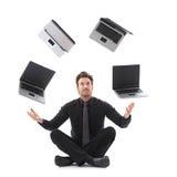 玩杂耍与膝上型计算机的生意人 免版税库存图片