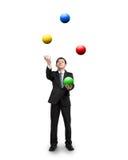 玩杂耍五颜六色的球的黑衣服商人 图库摄影