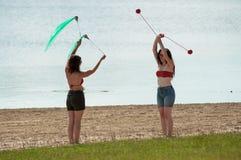 玩杂耍在海滩的两名妇女 免版税图库摄影