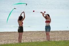 玩杂耍在海滩的两名妇女 图库摄影