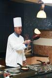 玩杂耍用在平底锅的薄煎饼的厨师 免版税库存图片