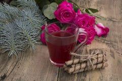玫瑰、冷杉木分支和一个杯子汁液在中心 免版税库存照片