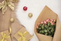 玫瑰、圣诞节球和礼物大豪华花束在毛皮地毯 寒假概念 免版税库存照片