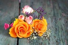 玫瑰五颜六色的花束在一张老木桌上的 图库摄影