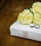 玫瑰和圆环在白色圣经 免版税库存图片