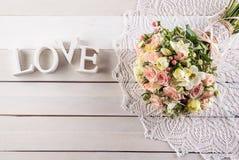 玫瑰和小苍兰美丽的婚礼花束与信件在白色木背景、背景华伦泰的或婚礼之日 免版税库存照片