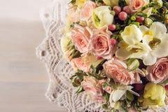 玫瑰和小苍兰美丽的婚礼花束与鞋带在白色木背景、背景华伦泰的或婚礼之日 免版税库存照片