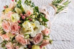 玫瑰和小苍兰美丽的婚礼花束与鞋带在白色木背景、背景华伦泰的或婚礼之日 图库摄影