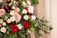 玫瑰和日工在花瓶在桌特写镜头 免版税库存图片