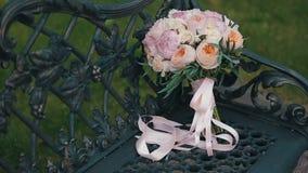 玫瑰和牡丹婚礼花束在用金属葡萄树装饰的一条古板的黑金属长凳 brewster 影视素材