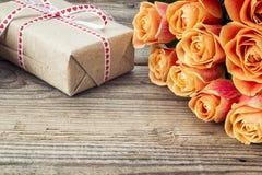 玫瑰和礼物盒花束在一张老木桌上 复制空间 免版税库存图片