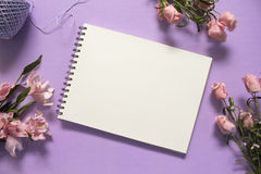 玫瑰和空白页平的位置在紫罗兰色背景 浪漫桃红色花花束 免版税图库摄影