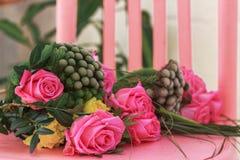 玫瑰和花束在一把桃红色椅子 免版税库存照片