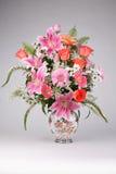 玫瑰和莉利亚在桌上的花瓶开花 免版税库存图片