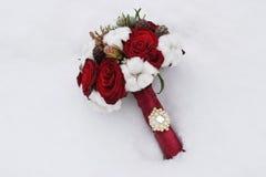 玫瑰和锥体花束在雪 免版税库存照片