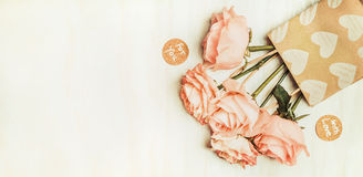玫瑰在与爱消息标志的在轻的背景,顶视图的购物袋和心脏 免版税库存照片