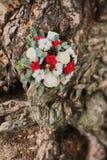 玫瑰婚姻的花束与红色丝带的在一棵树的根在森林里 库存图片