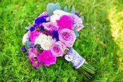 玫瑰婚礼花束在紫色口气的 植物的构成 图库摄影