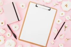 玫瑰开花与剪贴板、笔记本和黑笔在桃红色背景 平的位置,顶视图 自由职业者企业概念 免版税库存照片