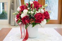 玫瑰开花在花瓶里面的花束在房子装饰的书桌上 库存图片