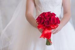 玫瑰明亮的红色花束在新娘的手,关闭上 库存图片
