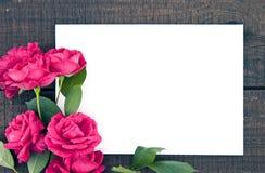 玫瑰框架在黑暗的土气木背景的与空的卡片 库存照片