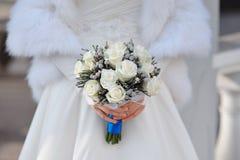玫瑰白色婚礼花束在新娘的手上 库存图片