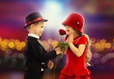 给玫瑰的可爱的小男孩女孩 免版税库存图片