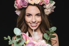 玫瑰的愉快的迷人的年轻女性缠绕拿着美丽的花束 免版税库存图片