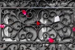 玫瑰的瓣在伪造的格子的进口前面驱散 免版税库存照片