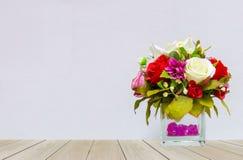 玫瑰的美好的多颜色在玻璃花盆的在木表上的角落有灰色背景 库存照片
