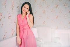 玫瑰礼服手机谈话的少妇 智能手机电话 女孩微笑和谈话与手机 库存照片