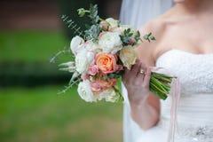 玫瑰美丽的婚礼花束在手上  免版税图库摄影