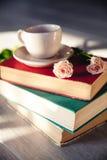 玫瑰美丽的花束在阳光下在与杯子的书 免版税库存图片