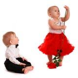 玫瑰色女孩红色裙子的舞蹈和男孩绅士爱,华伦泰的D 免版税库存照片