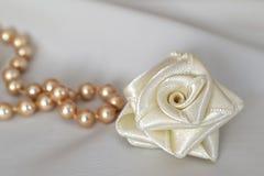 玫瑰色手工制造的丝绸和珍珠 免版税库存照片