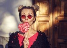 玫瑰色玻璃的白肤金发的女孩舔棒棒糖的 图库摄影